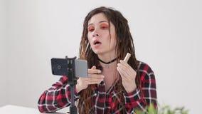 Concept blogging en videouitzendingen De jonge vrouwelijke video of de uitzending van de bloggeropname levend op smartphone stock videobeelden