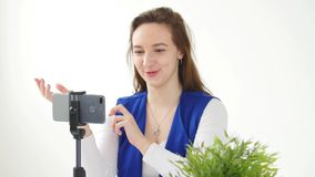 Concept of blogging and video broadcasts. Young female blogger recording video or broadcast live on smartphone. At home stock video footage
