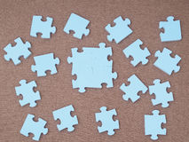 Concept of blue puzzle pieces on brown background Stock Photos