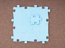 Concept of blue puzzle pieces on brown background Royalty Free Stock Images