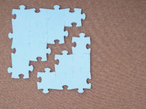 Concept of blue puzzle pieces on brown background Stock Image