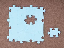 Concept of blue puzzle pieces on brown background Royalty Free Stock Photo