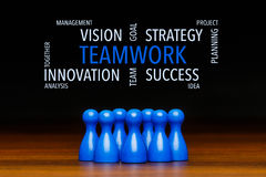 Concept blue teamwork text cloud. Concept for: teamwork, team, working together, goal, success. Containing text cloud with business words. With blue pawn figures Stock Photography