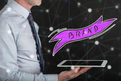 Concept of brand. Brand concept above a tablet held by a man royalty free stock images