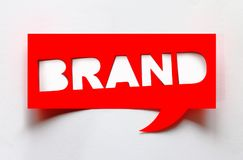 Concept of brand. Creative brand word cut from paper isolated on white background royalty free stock image