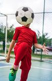 Concept of Brazilian soccer. Child soccer player juggling ball with his knee on the sports court Stock Photos