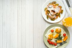 Concept of Breakfast. Fried eggs, cottage cheese pancakes, plums and oatmeal with milk, orange juice on the table.  royalty free stock images