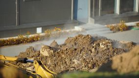Concept of the breakthrough of underground utilities. steam breaks out of the ground. Excavator digs a hole to determine. The location of the breakthrough of stock footage