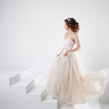 Concept of bride going towards future happiness. Beautiful girl in a wedding dress. Royalty Free Stock Image