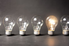 Concept of bright idea with series of light bulbs Stock Images