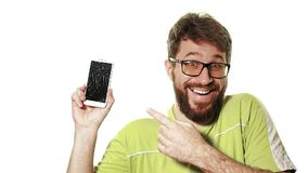 The concept of a broken gadget. A bearded man shows the smartphone with a broken screen. He`s laughing hysterically