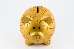 Concept of broken gold piggy bank. Front side of gold piggy bank cracked on isolated white background Royalty Free Stock Image