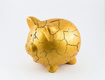 Concept of broken gold piggy bank. Left side of gold piggy bank cracked on isolated white background Royalty Free Stock Image
