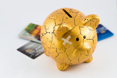 Concept of broken gold piggy bank. Right side of gold piggy bank cracked with plaster and blurred credit cards on isolated white background Stock Photography