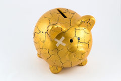 Concept of broken gold piggy bank. Right side of gold piggy bank cracked with plaster on isolated white background Royalty Free Stock Image