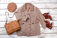 Concept of brown winter clothing. Beige camel coat, handbag, hat and shoes. White desk wooden background Royalty Free Stock Photos