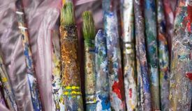 Concept of brushes soiled in colorful paints Royalty Free Stock Photos