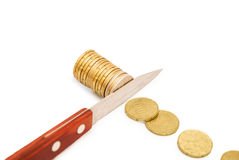 Concept of budget cuts, savings, recession. Knife cutting a pile of coin. Concept of budget cuts, savings, recession royalty free stock photos