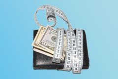 Concept of budget and money. Money with purse is tied with measuring tape Royalty Free Stock Photography