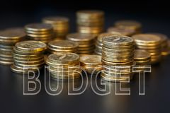 The concept of budgeting. The word Budget is made up of transparent letters located on piles of coins. The concept of budgeting royalty free stock images