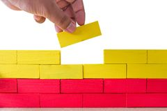 Concept of building success foundation, Hand on the last yellow. Puzzle wooden blocks in the shape of a wall isolated white background Royalty Free Stock Image