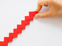 Concept of building success foundation. Women hand put red puzzle wooden blocks in the shape of a staircase Stock Photos
