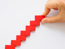 Concept of building success foundation. Women hand put red puzzle wooden blocks in the shape of a staircase Royalty Free Stock Images