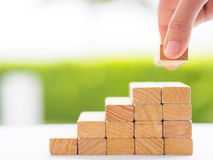 Concept of building success foundation. Women hand put wooden blocks in the shape of a staircase Stock Photos