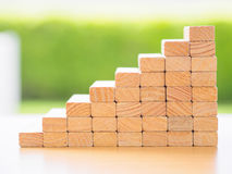 Concept of building success foundation. Women hand put wooden blocks in the shape of a staircase Royalty Free Stock Photography