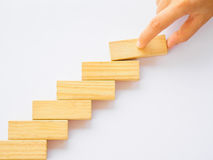 Concept of building success foundation. Women hand put wooden blocks in the shape of a staircase Stock Image