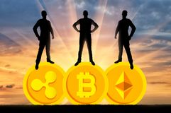 Concept of business in the crypto currency. Three businessmen are standing on three coins of the crypto currency. The concept of business in the crypto currency Stock Photography