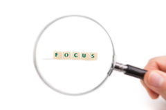 Concept of business idea focus. Magnifying glass in hand on the letters. Stock Image