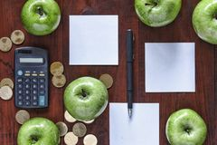 Concept: business, investment, enrichment, logistics, planning. Green apples, gold coins, calculator and paper for entries on th stock photo