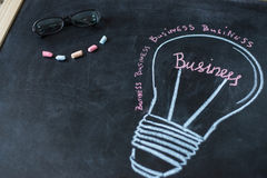 Concept - business light bulb drawn with chalk on a blackboard Stock Photos