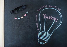 Concept - business light bulb drawn with chalk on a blackboard Royalty Free Stock Photo