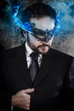Concept business, man with fiery eyes and Venetian mask wearing. Black dress, office Royalty Free Stock Photography