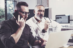 Concept of business people brainstorming process.Bearded young man using mobile phone and adult colleague looking to Stock Photos