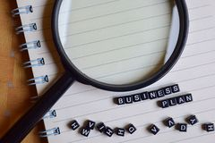 Concept of Business Plan word on wooden cubes with magnifying glass, books in background stock photos