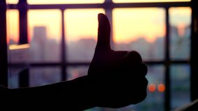 Concept of business. Silhouette hand gesture like against the evening blurred city with bokeh during sunset. 4k. Concept of business. Silhouette hand gesture stock video
