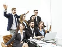 Concept of business success - cheering business team in the workplace in the office Royalty Free Stock Images