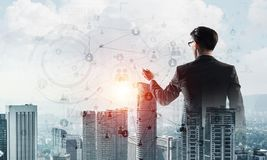 Concept of business success and control with confident boss against cityscape background stock images