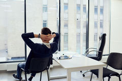 The concept of business success is a dream vacation relax. Young. Businessman hands behind his head resting in a modern office stock image