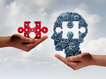 Concept Of Business Training. And skill development symbol as human hands holding a puzzle piece and gears shaped as a head as a technology or training metaphor Stock Photography