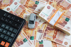 The concept of buying a car: model cars, a calculator and a stack of Russian rubles in the banking package lying on the background Stock Image