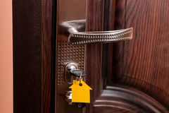 The concept of buying a home. Keys with keychain house in the door lock close-up stock image