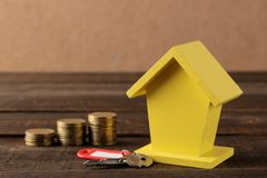 The concept of buying a home. Yellow decorative house and money and keys on a brown background with a place for an inscription stock images