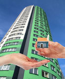 Concept of buying a house. Hand giving small house model to the other hand, modern building in the background Royalty Free Stock Image
