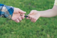 Concept of buying a new house. Man holding a key. Woman giving a key Royalty Free Stock Images