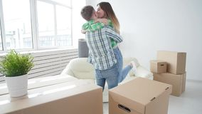 Concept of buying and renting real estate. Lucky couple embracing in new house. Concept of buying and renting real estate. Lucky young couple embracing in new stock footage