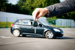 Concept of buying, selling and renting a car. A female hand hold. S the car key against the background of the car. With a place for advertising text Royalty Free Stock Images